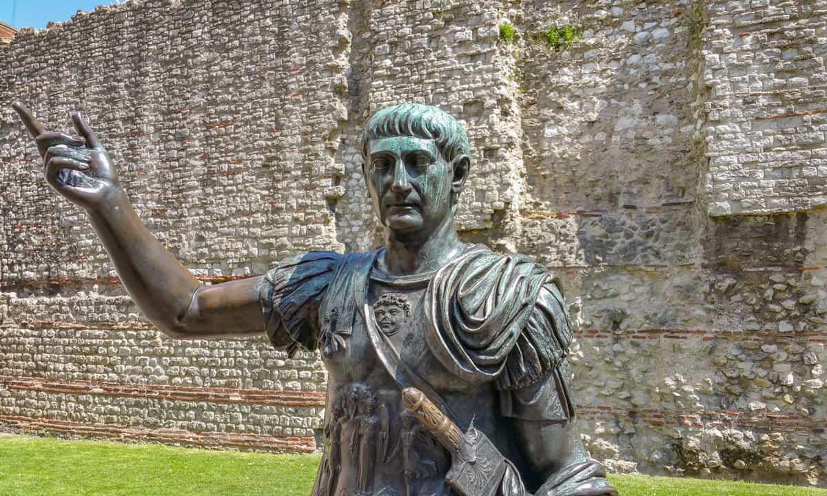 A bronze statue in front of a section of the Roman wall in London.