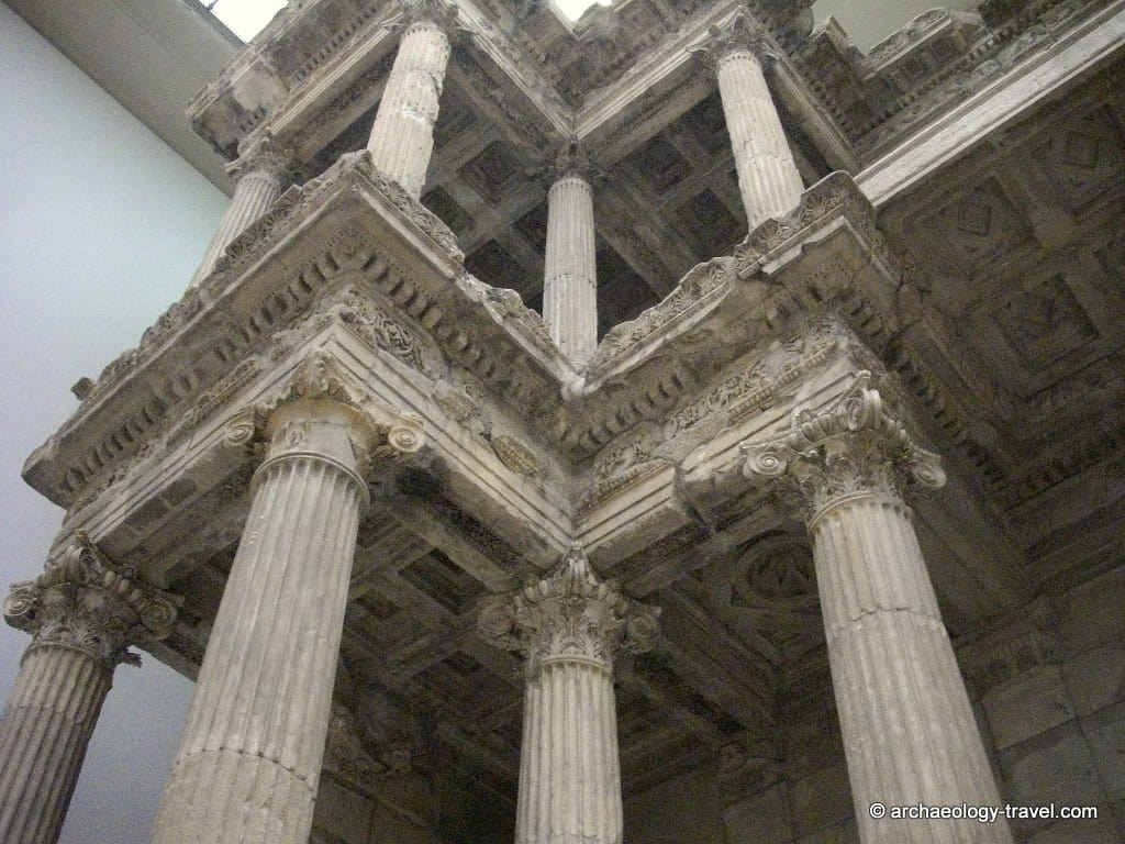 A close up of the detailed pediment that is supported by Corinthian columns.
