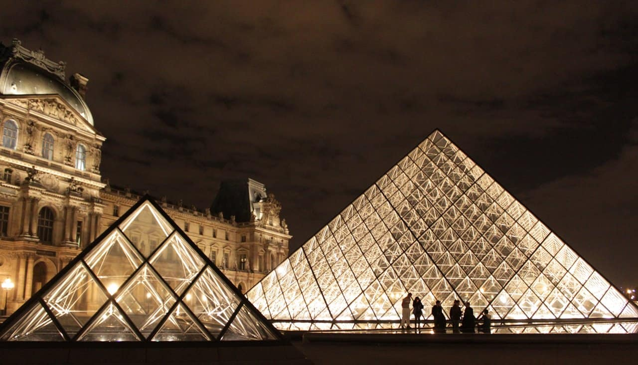 The glass pyramids at the Louvre by night.