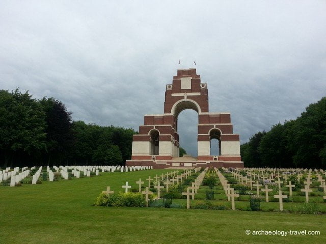 Unknown French and Commonwealth tombstones in front of the Thiepval Memorial under a thundery sky.
