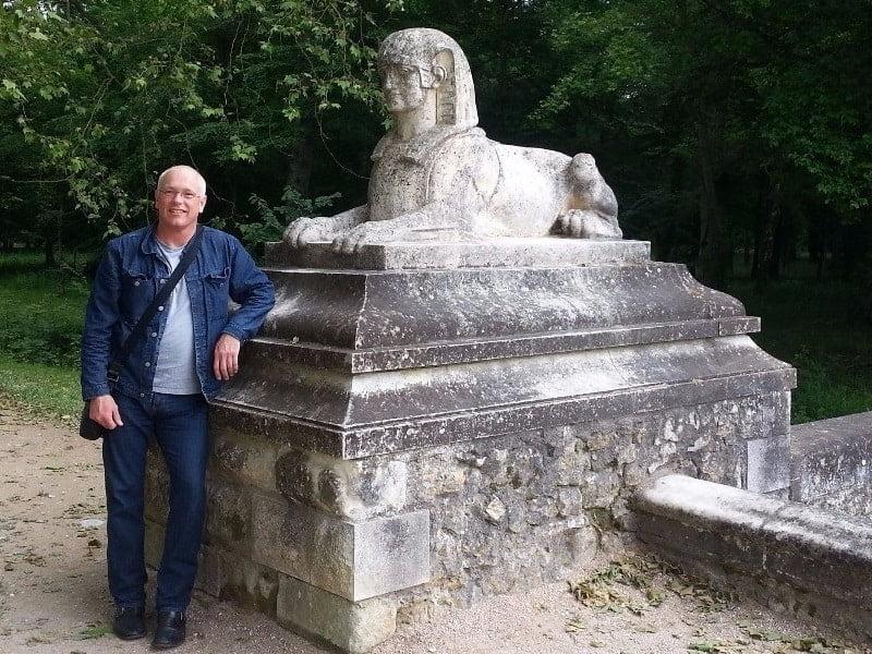 Thomas Dowson beside one of René de Villeneuve's sphinxes, Chenonceau Castle, France.