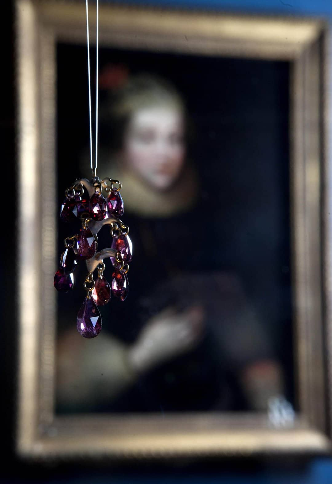 A garnet pendant hangs in front of a portrait of Elizabeth Wriothesley wearing the kind of jewellery on display.