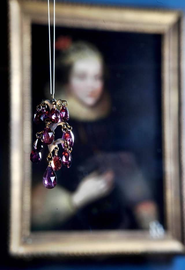 A garnet pendant hangs in front of a contemporary portrait.