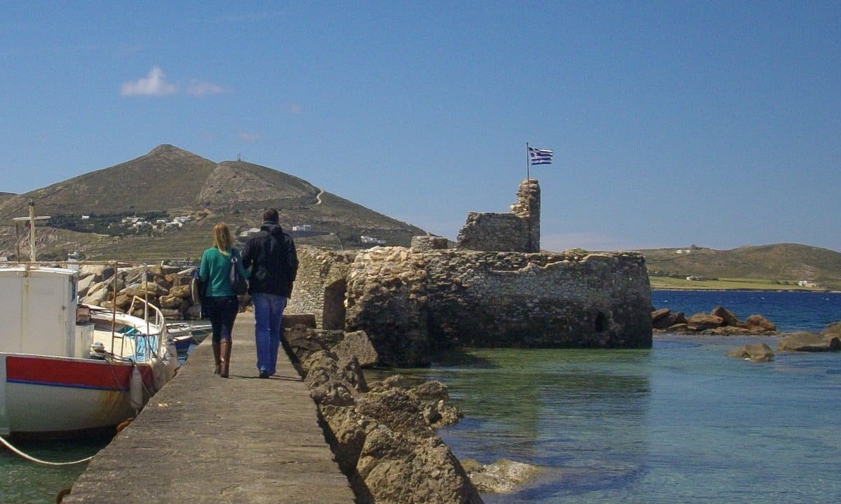 A couple walk towards the Venetian fort in the port of Naoussa, Paros.