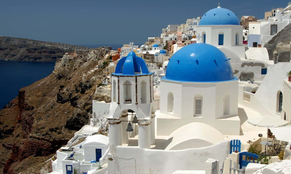 Brilliant white buildings and blue domes of churches on the volcanic caldera at Santorini.