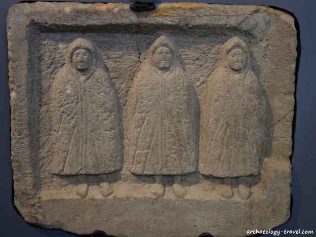 Three hooded spirits, known as genii cucullati, from the vicus at Housesteads.