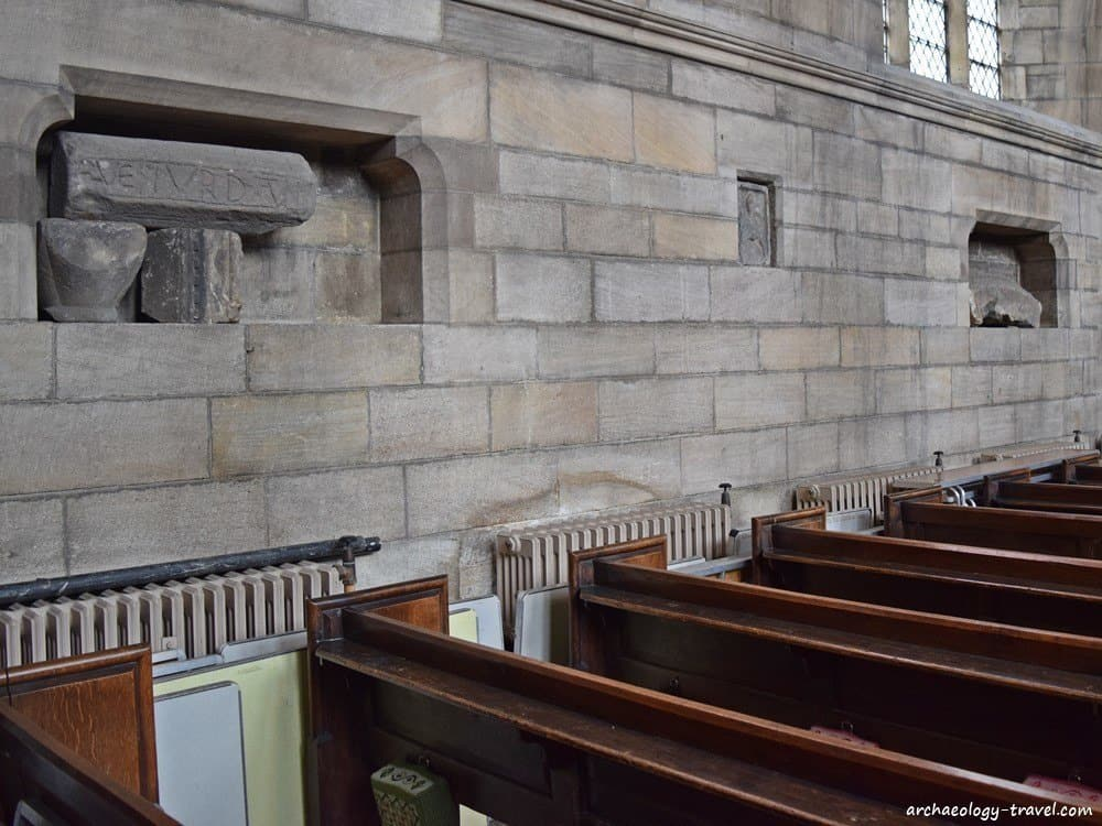 Spolia are placed within niches  in the nave wall.