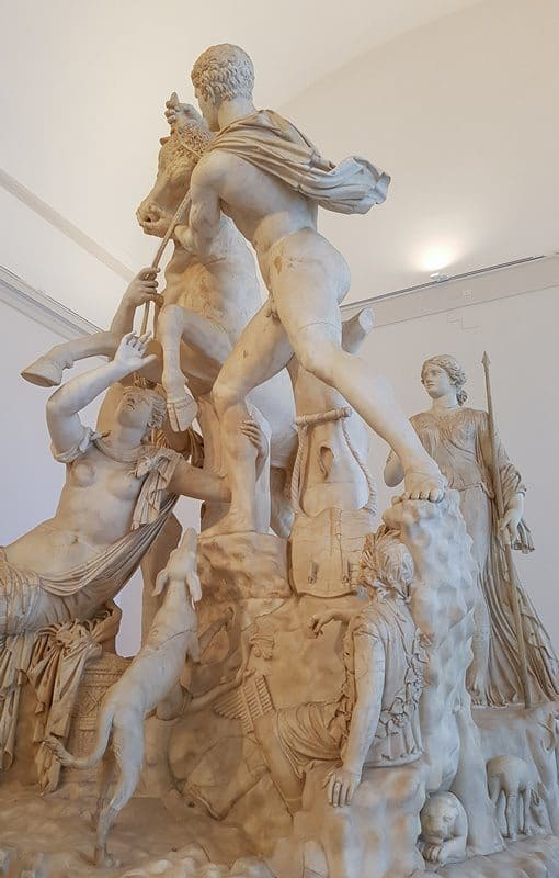 A close up of the Farnese Bull sculpture, showing the shepherd and his excited dog.