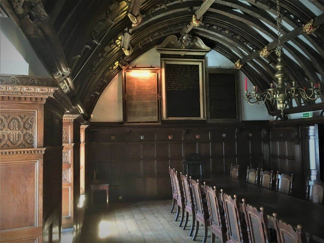 Another view of Tuckers Hall Exeter with chandelier and wooden panelling.
