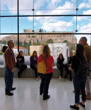 A guide showing visitors around the Acropolis museum.