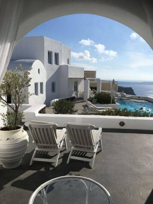 A view over a patio with two loungers with a pool and the sea in the distance.