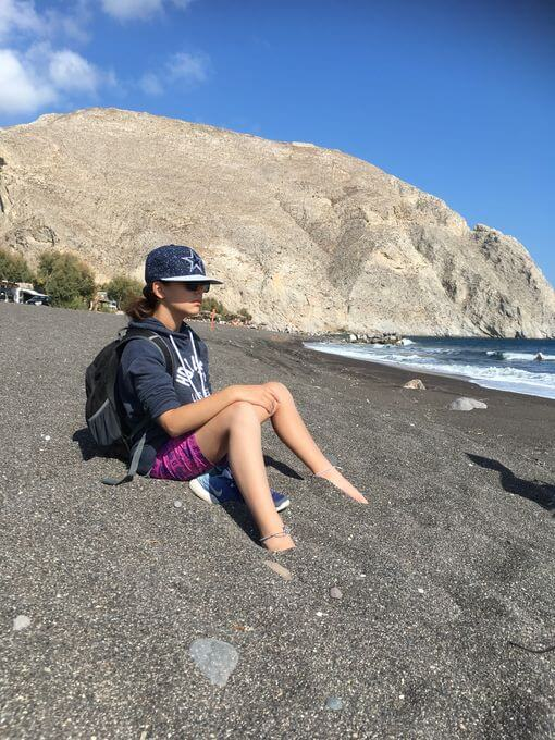 A girl sitting on a black sand beach with a cliff behind and blue sky.