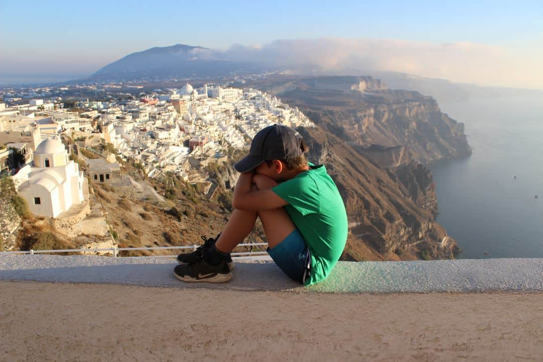 A boy sitting on a wall resting his head on his legs with cliffs and a view in the background.