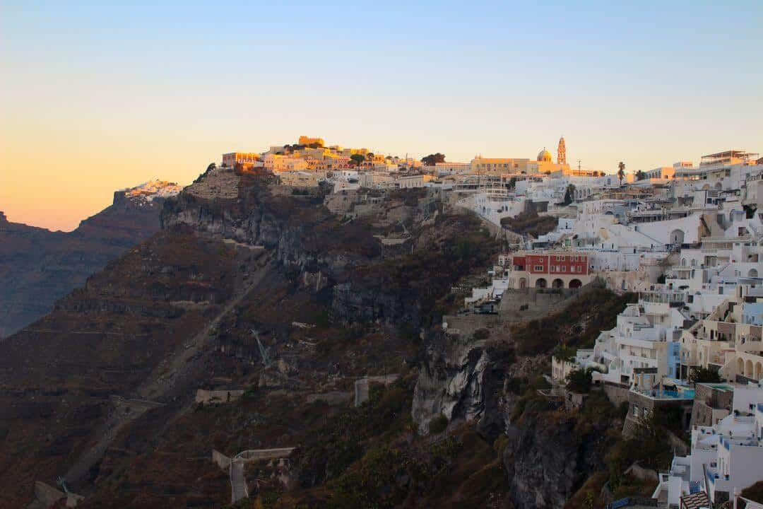 Whitewashed villas on a cliff top with the colours of sunrise in the sky.