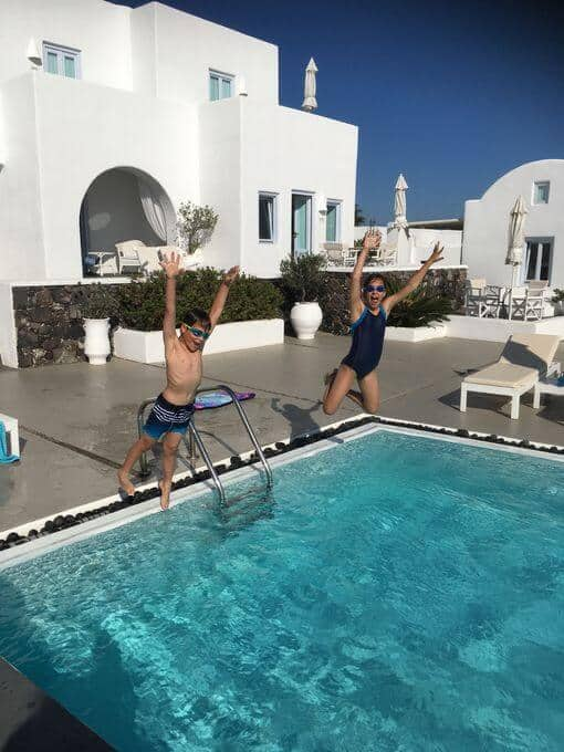 Two kids jumping into a swimming pool in front of a whitewashed building.