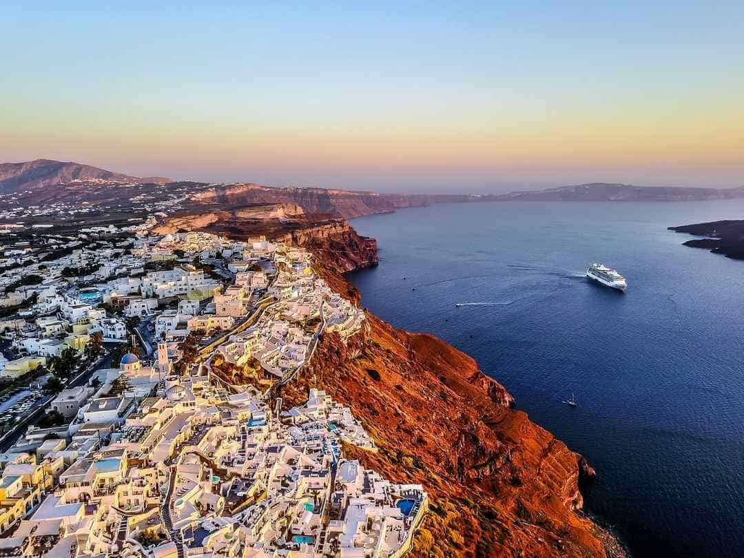 A view taken from a drone over the island with lots of white houses on top of a high cliff, a cruise ship in the sea.
