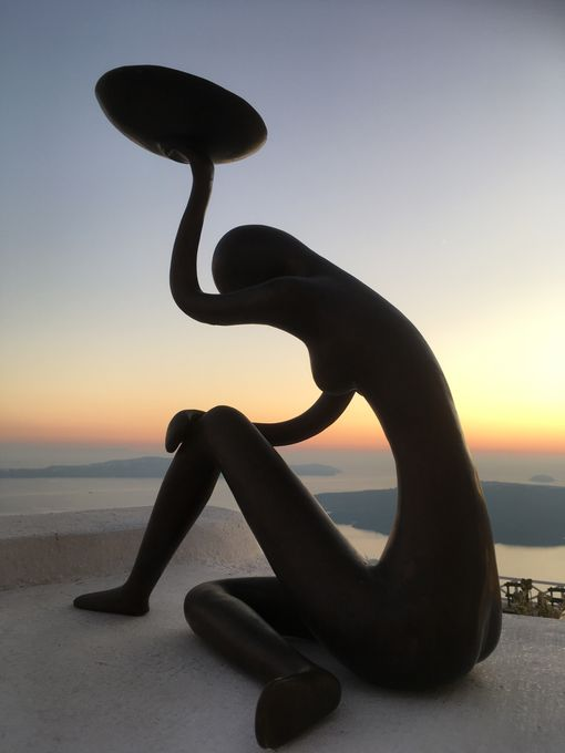 A sculpture on a wall against the sea and a colourful sunset.