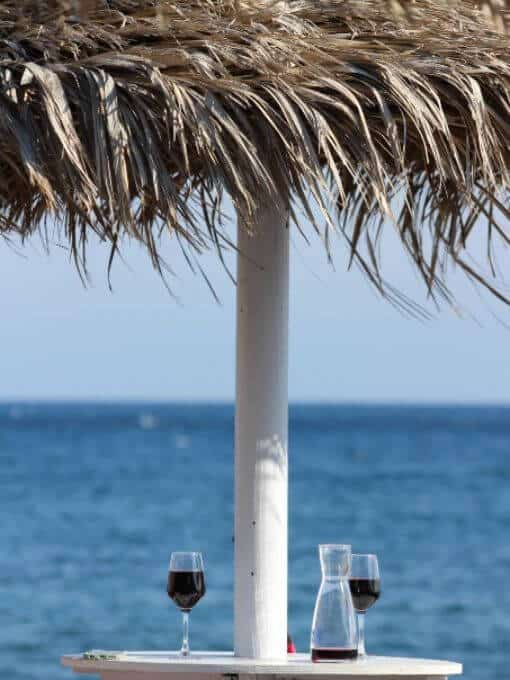 A table and beach umbrella with a carafe and two glasses of red wine on it.
