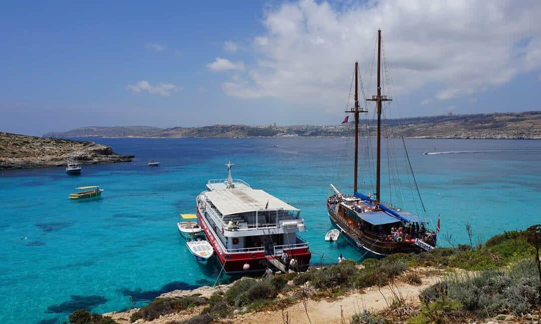 View of tour boats in the blue waters around Comino.