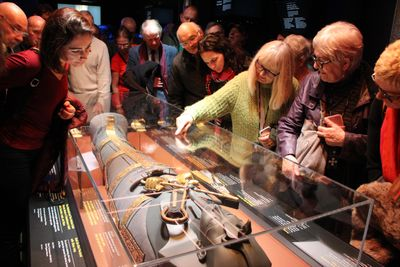 A crowd of people looking at a Tutankhamun mock up in a glass case.