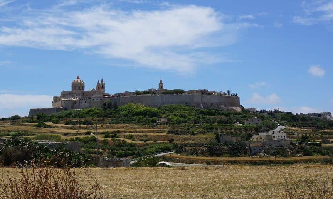 The city of Mdina, Malta, from afar showing the thick walls, domes and spires.