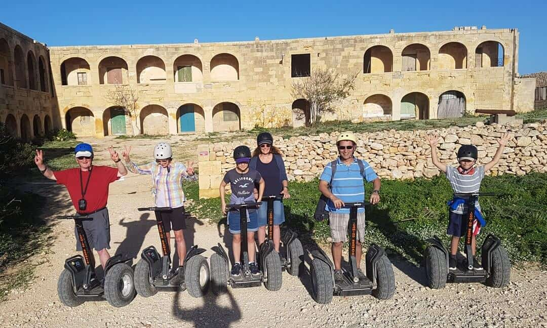 A family on segways in front of the old hospital on Comino.