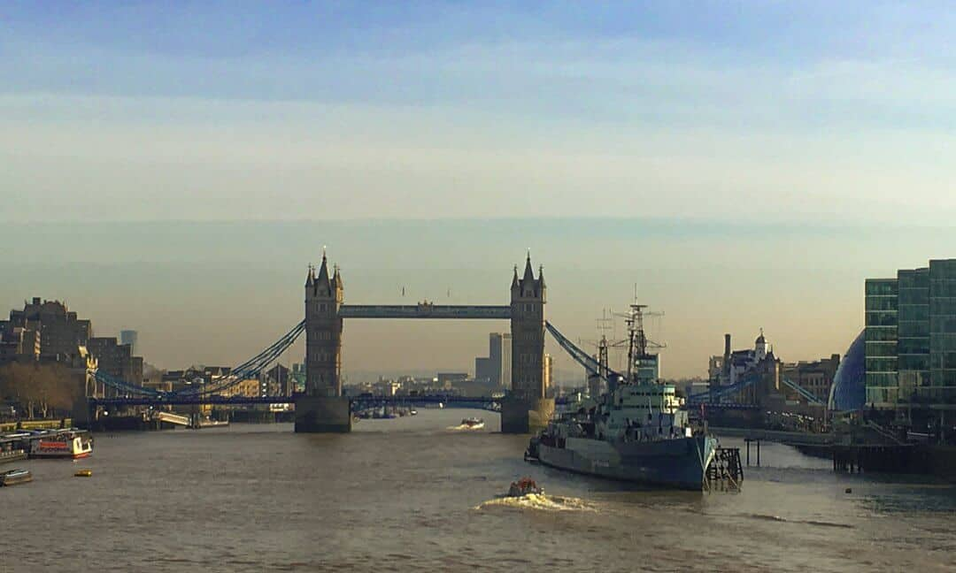 A panoramic view of HMS Belfast on the River Thames with Tower Bridge in the background.