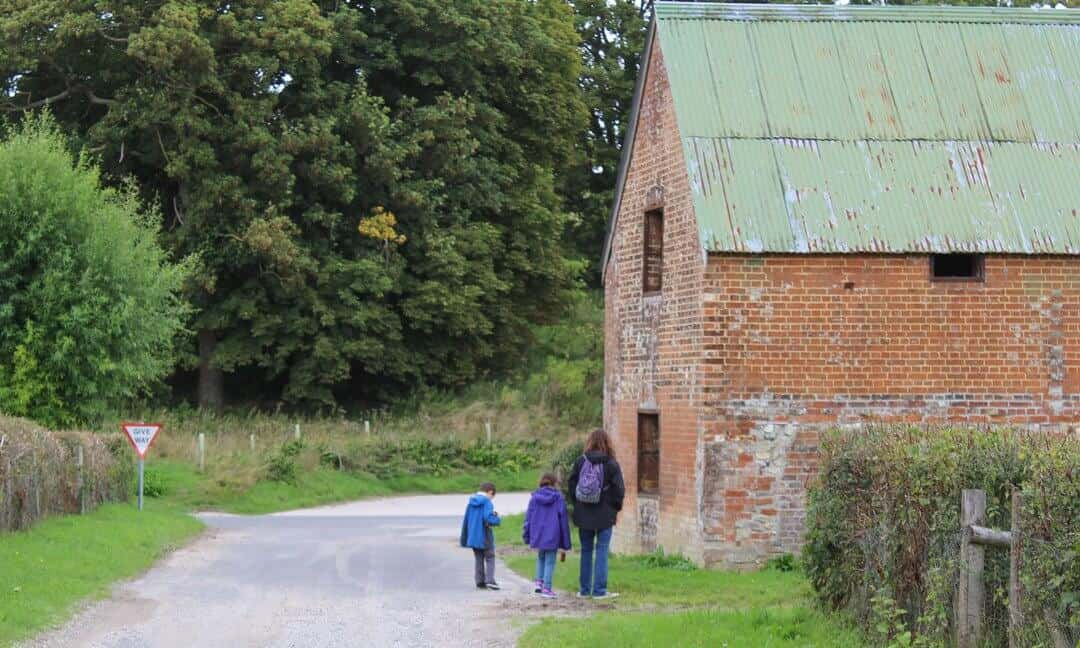 My family looking into a derelict building with tin roof is by the side of the road in Imber.