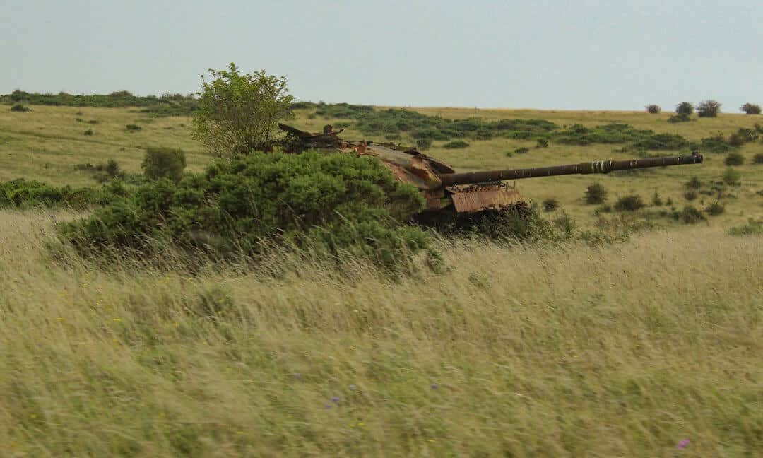 A rusted tank behind bushes on Salisbury Plain.