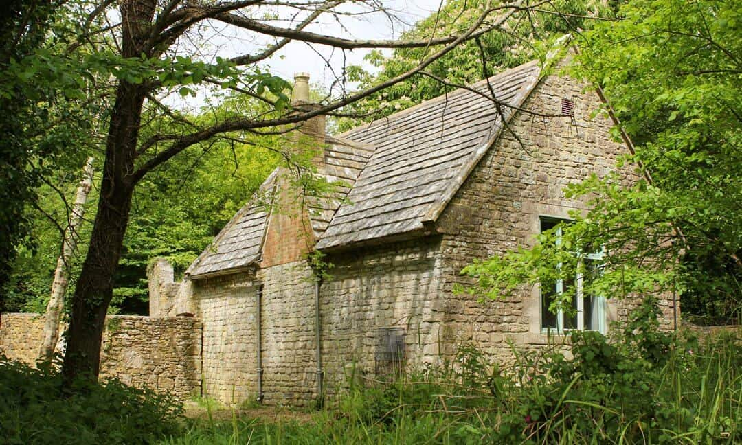 The complete structure of the Tyneham schoolhouse surrounded by trees and vegetation.