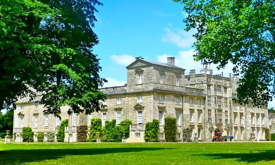 The exterior of Wilton House surrounded by trees on a sunny day.