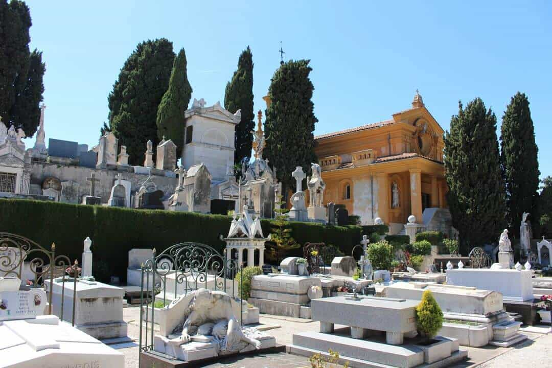 White marble monuments and graves are packed together next to a small chapel and trees