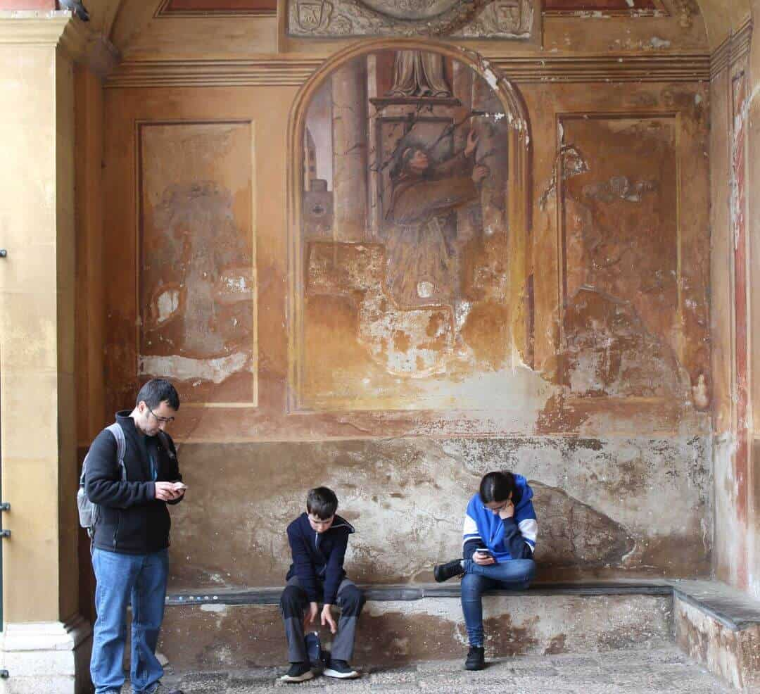 My family looking at their phones in front of a fresco outside the church.