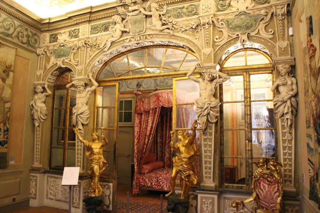 Inside a bedroom at the palace with baroque decoration, statues and gilt.