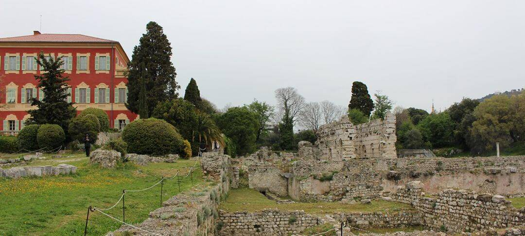 The ruins of the archaeological site against a grey sky, trees and a red building in the background.