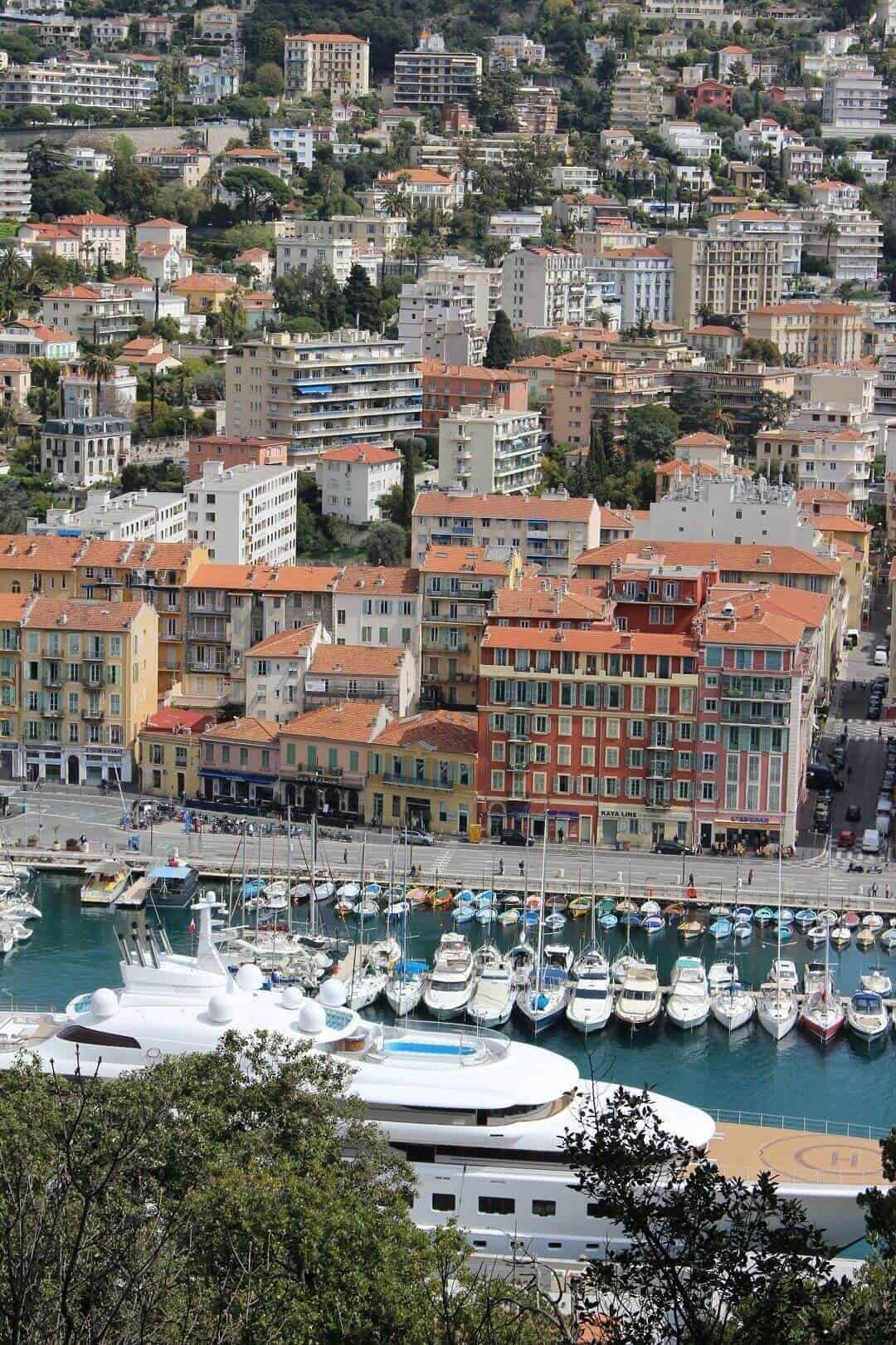 The super yacht in the foreground with small boats in the harbour and buildings rising behind them all.