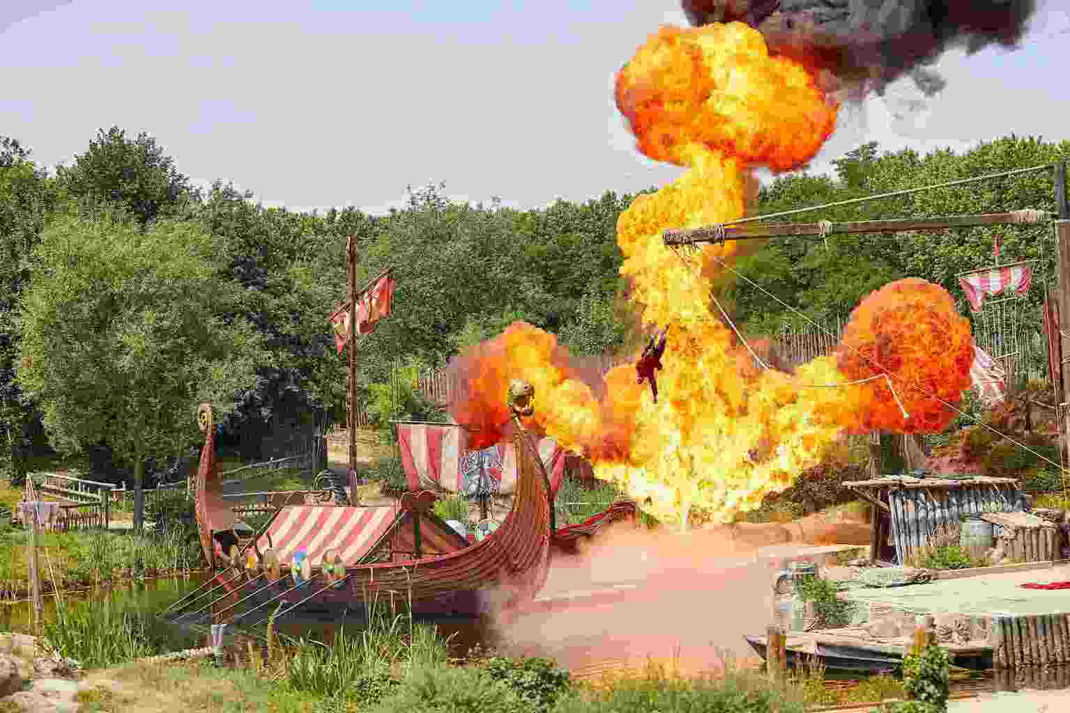 A stunt man leaping out of a Viking ship with a huge explosion behind him.
