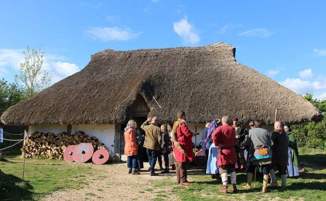 A group of people most of them dressed as Saxons outside a white thatched building.