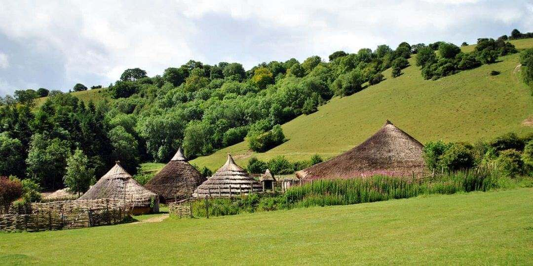 Thatched roofs of roundhouses against a tall hill in the background covered in grass and trees.
