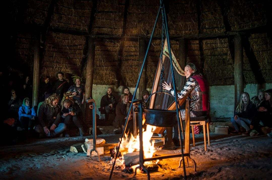 A lady playing a Celtic harp behind an open fire with people sitting around her watching.