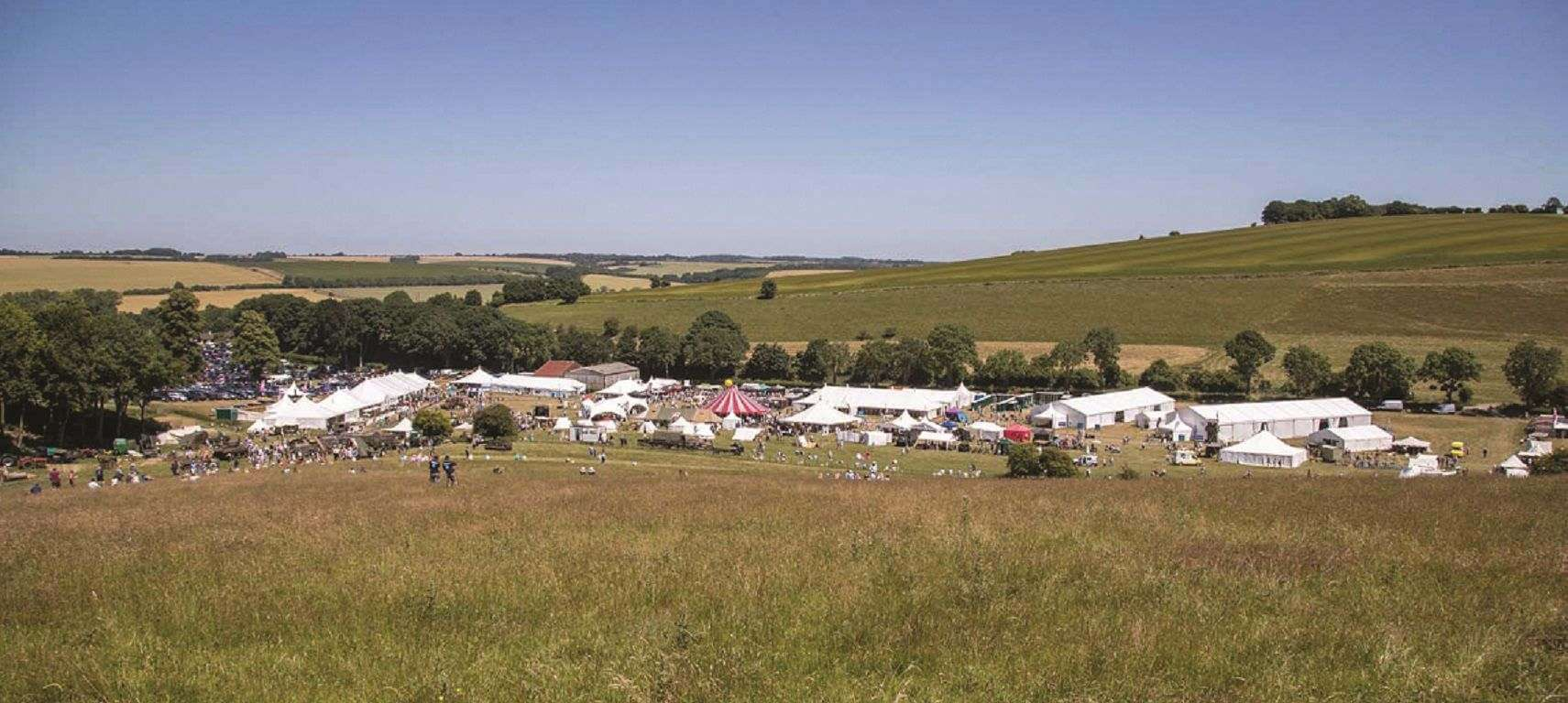 A view across hills and fields with the white tents of the festival.