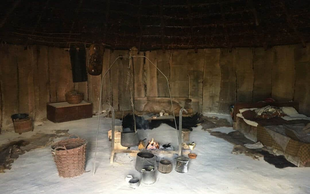 Inside the roundhouse showing a white floor, wooden wall, a bed covered in animal skins, a pot over an open fire and various pots and baskets.