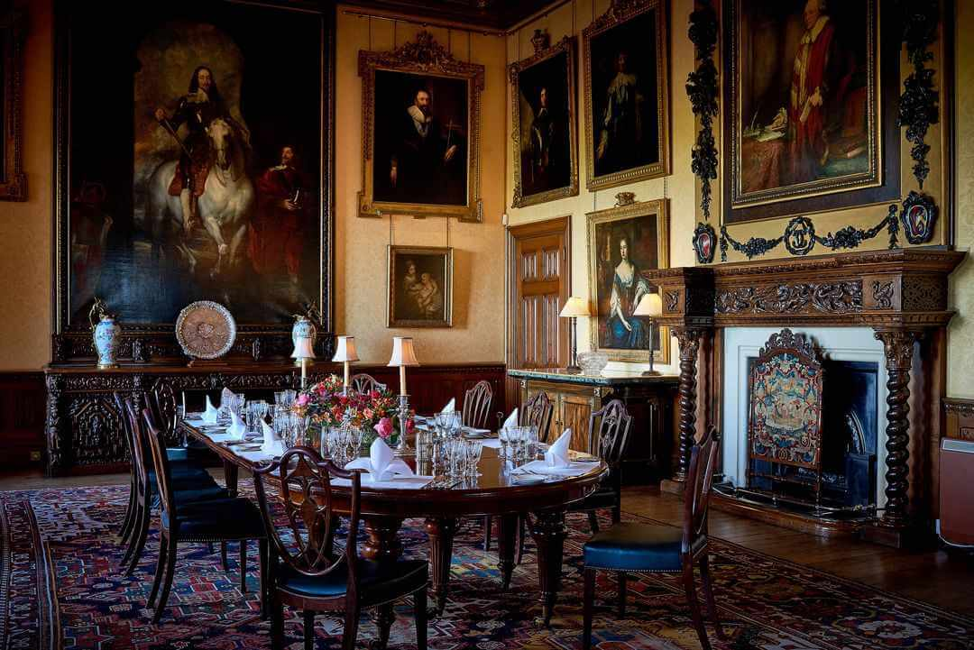 Inside the dining room showing table laid for dinner, portraits on the walls and wooden fireplace and sideboards.