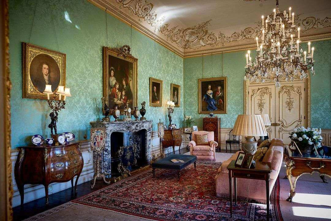 The green silk walls and crystal chandelier in the drawing room.