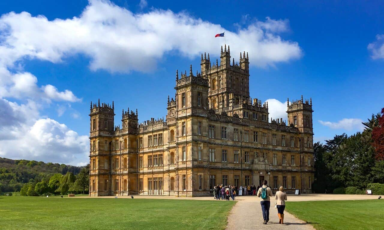 The famous outside view of Highclere castle on a sunny day with people walking towards it.