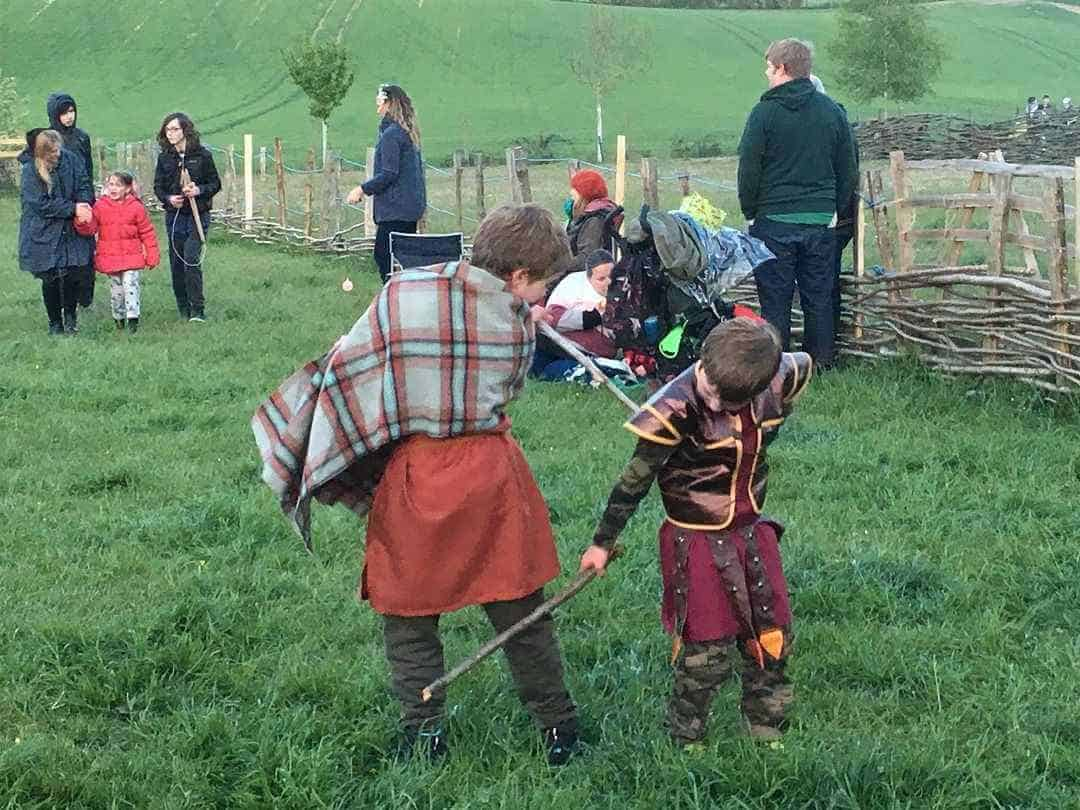 Two young children in Saxon costume having a sword fight.