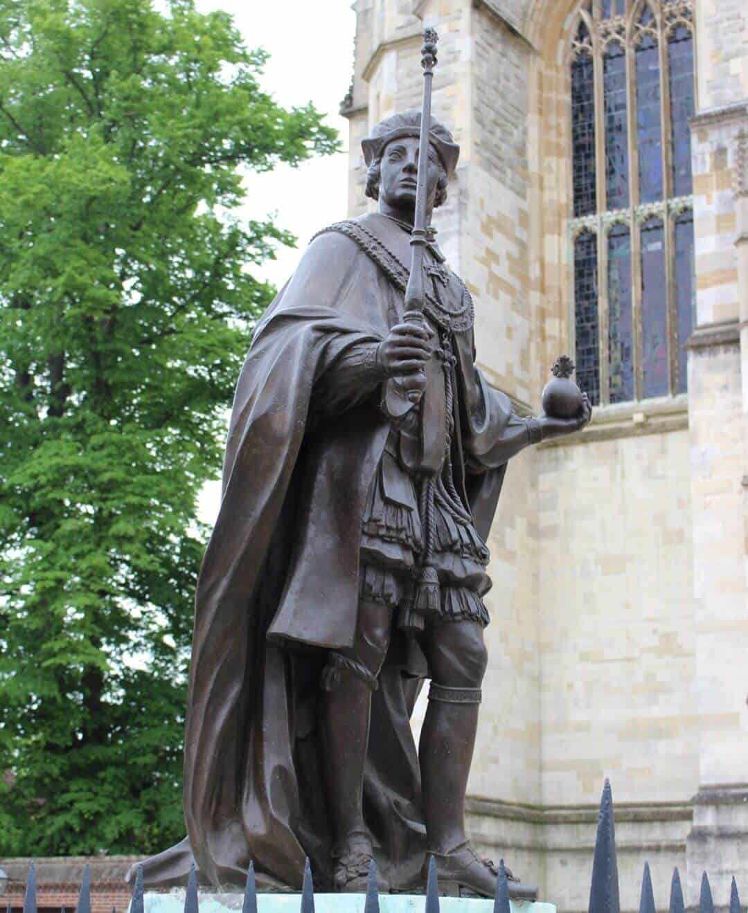 The statue of King Henry VI in close up showing he is holding an orb and spectre.