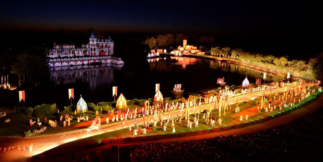 A view over the lake showing the show in action with bright lights and illuminated castle in the background.