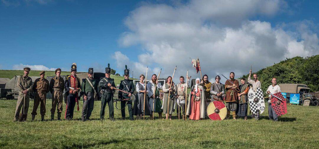 A line of people all in different period costumes looking at the camera, in a field against a blue sky.