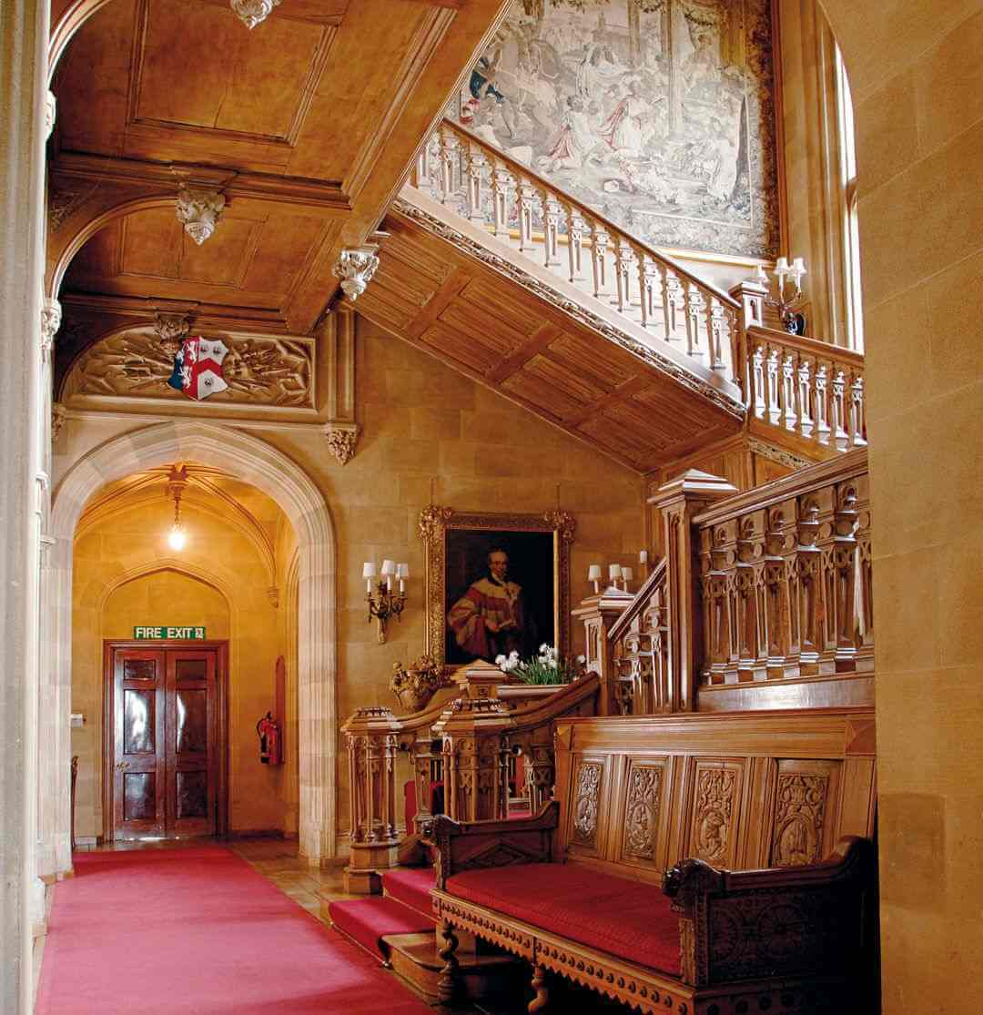 The staircase taken from the ground floor showing tapestries, portraits and a carved wooden bench.